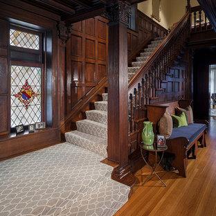 ニューヨークの広いカーペット敷きのヴィクトリアン調のおしゃれな折り返し階段 (木の蹴込み板、木材の手すり) の写真