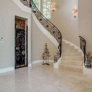 Неиссякаемый источник вдохновения для домашнего уюта: изогнутая лестница в средиземноморском стиле с ступенями из травертина, подступенками из травертина и металлическими перилами