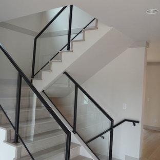 Imagen de escalera en U, de estilo americano, de tamaño medio, con escalones de madera, contrahuellas de madera y barandilla de vidrio