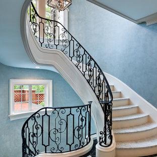 Idee per una grande scala curva chic con alzata in legno, pedata in marmo e parapetto in metallo