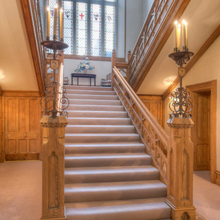 This is an example of an expansive midcentury carpeted staircase in Devon with carpet risers.