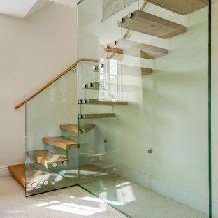 Стильный дизайн: угловая лестница среднего размера с деревянными ступенями и стеклянными подступенками - последний тренд