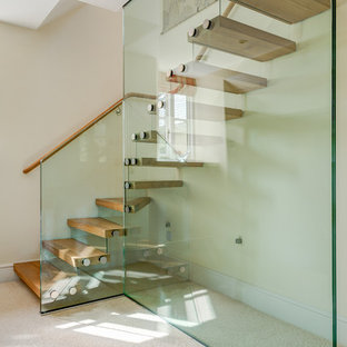 Mid-sized wooden l-shaped staircase photo in Devon with glass risers
