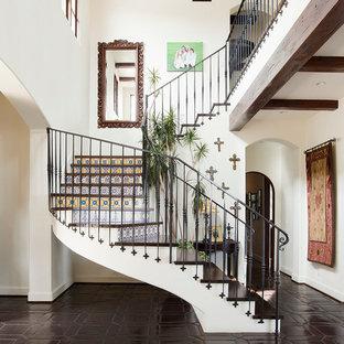 Ejemplo de escalera curva, mediterránea, con escalones de madera y contrahuellas con baldosas y/o azulejos