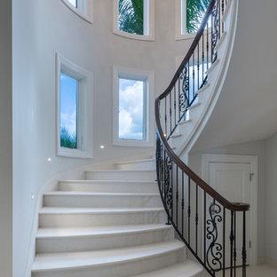 Foto på en stor vintage svängd trappa i marmor, med sättsteg i marmor