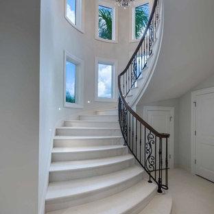 Inspiration för en mycket stor medelhavsstil svängd trappa i travertin, med sättsteg i travertin och räcke i flera material