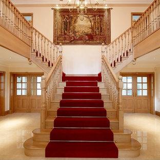 Idée de décoration pour un très grand escalier droit tradition avec des marches en bois et des contremarches en bois.