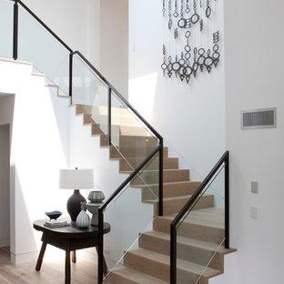 Imagen de escalera costera, grande, con escalones de madera, contrahuellas de madera y barandilla de vidrio