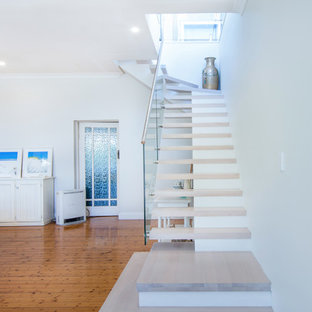 Mid-sized coastal wooden curved mixed material railing staircase photo in Sydney with glass risers