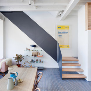 Inspiration for a contemporary wood metal railing staircase in London with open risers.