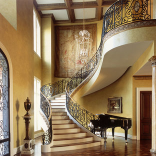 This is an example of a large victorian wood curved metal railing staircase in Austin with painted wood risers.