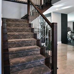 他の地域の中くらいのカーペット敷きのコンテンポラリースタイルのおしゃれなかね折れ階段 (木の蹴込み板、混合材の手すり) の写真