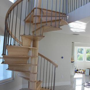 他の地域の小さい木のトランジショナルスタイルのおしゃれならせん階段 (木の蹴込み板、混合材の手すり) の写真