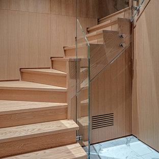 Idee per una piccola scala moderna con pedata in legno e parapetto in vetro