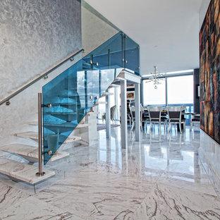 Cette image montre un escalier sans contremarche flottant design de taille moyenne avec des marches en marbre et un garde-corps en verre.