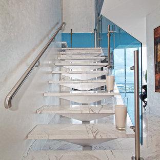Foto de escalera suspendida, contemporánea, de tamaño medio, sin contrahuella, con escalones de mármol y barandilla de vidrio