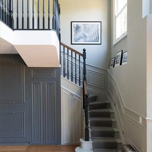 Diseño de escalera curva, tradicional, con escalones de madera pintada y contrahuellas de madera pintada