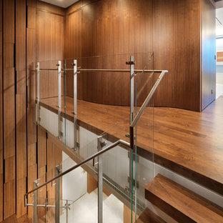 Ispirazione per una scala minimalista con pedata in legno e parapetto in vetro