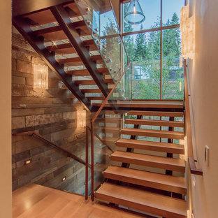 Ejemplo de escalera en U, rústica, grande, sin contrahuella, con escalones de madera y barandilla de vidrio
