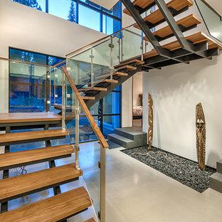 Esempio di una grande scala sospesa design con pedata in legno e nessuna alzata