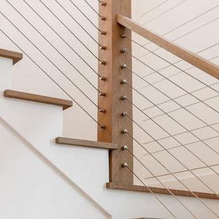 """Foto di una scala a """"L"""" stile marino di medie dimensioni con pedata in legno, alzata in legno verniciato e parapetto in cavi"""