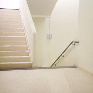 他の地域の大きいタイルのトラディショナルスタイルのおしゃれな折り返し階段 (タイルの蹴込み板) の写真