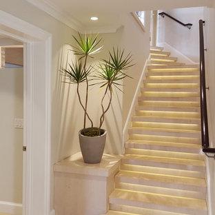 Ejemplo de escalera recta, exótica, de tamaño medio, con escalones de piedra caliza, contrahuellas de piedra caliza y barandilla de madera