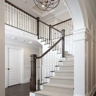 Ejemplo de escalera en L, tradicional renovada, grande, con escalones de madera, contrahuellas de madera pintada y barandilla de madera