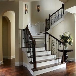 Modelo de escalera curva, clásica, con escalones de madera, contrahuellas de madera pintada y barandilla de varios materiales