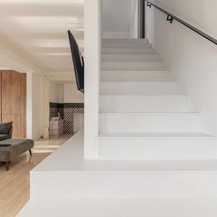 サリーの小さいタイルのヴィクトリアン調のおしゃれな直階段 (タイルの蹴込み板、金属の手すり) の写真
