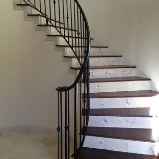 サンルイスオビスポの中サイズの木の地中海スタイルのおしゃれなサーキュラー階段 (タイルの蹴込み板、金属の手すり) の写真