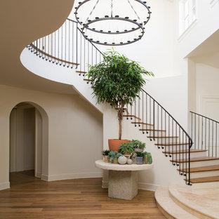 ロサンゼルスの木の地中海スタイルのおしゃれな階段 (フローリングの蹴込み板、金属の手すり) の写真