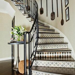 Пример оригинального дизайна: изогнутая лестница в средиземноморском стиле с деревянными ступенями и подступенками из плитки