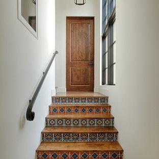 Immagine di una scala a rampa dritta mediterranea con pedata in legno e alzata piastrellata