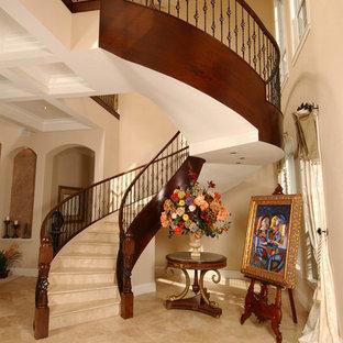 Ejemplo de escalera curva, mediterránea, con escalones de travertino, contrahuellas de travertino y barandilla de metal