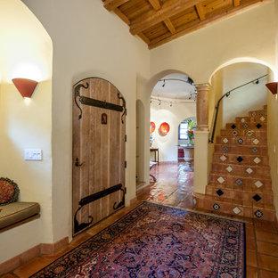 Неиссякаемый источник вдохновения для домашнего уюта: изогнутая лестница в средиземноморском стиле с ступенями из терракотовой плитки, подступенками из терракотовой плитки и металлическими перилами