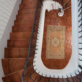 他の地域のテラコッタの地中海スタイルのおしゃれな階段 (金属の手すり) の写真