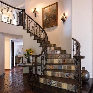 Foto de escalera curva, mediterránea, de tamaño medio, con escalones de madera, contrahuellas con baldosas y/o azulejos y barandilla de varios materiales