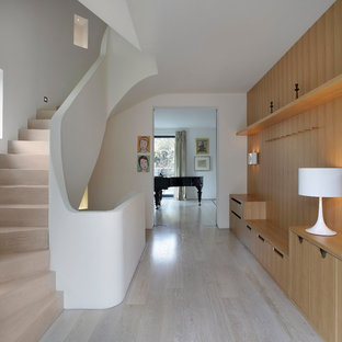Photo of a medium sized contemporary wood curved staircase in London with wood risers.