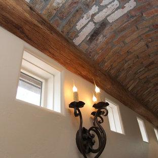 Diseño de escalera en L, mediterránea, con escalones de madera, contrahuellas de piedra caliza y barandilla de metal