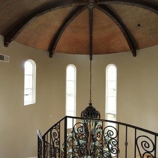 Ejemplo de escalera en L, mediterránea, con escalones de madera, contrahuellas de piedra caliza y barandilla de metal