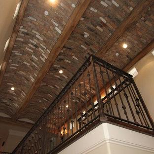 Modelo de escalera en L, mediterránea, con escalones de madera, contrahuellas de piedra caliza y barandilla de metal
