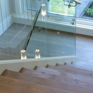 """Foto di una grande scala a """"U"""" minimal con pedata in legno, alzata in legno e parapetto in vetro"""