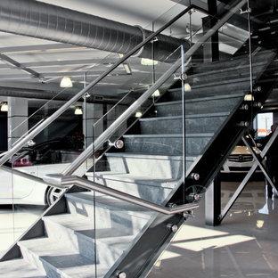 Ispirazione per un'ampia scala a rampa dritta minimalista con pedata piastrellata e alzata in vetro