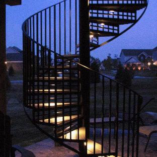 Esempio di una piccola scala a chiocciola design con pedata in legno, alzata in metallo e parapetto in metallo