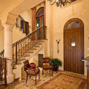 Cette image montre un très grand escalier courbe sud-ouest américain avec des marches en carrelage et des contremarches en bois.