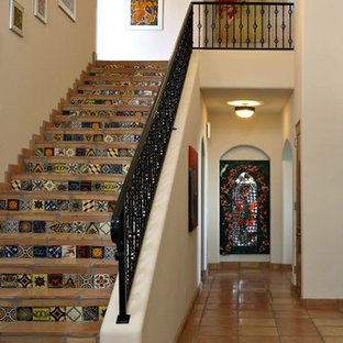 Ejemplo de escalera recta, de estilo americano, con escalones de terracota, contrahuellas con baldosas y/o azulejos y barandilla de metal