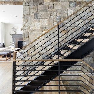 На фото: огромная п-образная лестница в современном стиле с деревянными ступенями и перилами из смешанных материалов без подступенок с