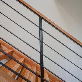Esempio di una scala sospesa minimal di medie dimensioni con pedata in legno, alzata in legno e parapetto in metallo