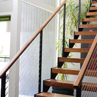 ニューヨークの中サイズの木のミッドセンチュリースタイルのおしゃれな階段 (ワイヤーの手すり) の写真